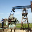 Stock Photo: Oil worker working on pump jack