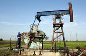 Oil worker working on pump jack — Stock Photo
