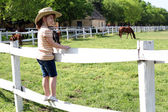 Little girl with cowboy hat standing on corral and watching hors — Stock Photo
