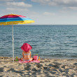 Little girl with hat sitting under sunshade on beach — Stock Photo #27620875