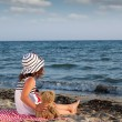 Little girl with teddy bear sitting on beach — Stok fotoğraf