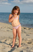 Happy little girl eat ice cream on beach — Stock Photo