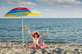 Happy little girl with hands up sitting under sunshade on beach — Stock Photo