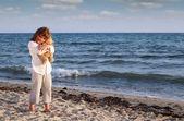Beautiful little girl with teddy bear on beach — Stock Photo