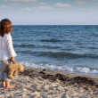 Little girl with teddy bear standing on beach and looking at the — Stock Photo #27926989