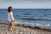 Little girl with teddy bear standing on beach and looking at the — Stock Photo