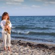Beautiful little girl with teddy bear on beach — Stock Photo