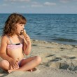 Little girl sitting on beach and eat ice cream — Stock Photo #28265355