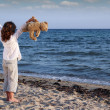 Happy little girl with teddy bear on beach — Stock Photo
