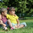 Boy and little girl sitting on grass in park — Stock Photo
