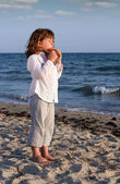 Beautiful little girl play pan pipe on beach — Stock Photo