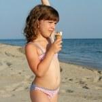 Child eat ice cream on beach — Stock Photo #28729009