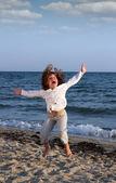Niño feliz saltando en la playa — Foto de Stock