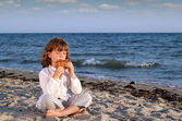 Beautiful little girl sitting on beach and play pan pipe — Stock Photo