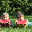 Happy boy and little girl with watermelon lying on grass — Stock Photo