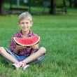 Happy boy with watermelon sitting on grass — Stock Photo