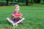 Happy boy with watermelon sitting on grass — 图库照片