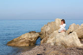 Little girl sitting on a rock by the sea and playing pan pipe — Stock Photo