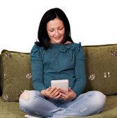 Dospívající dívka sedící na posteli a hrát si s počítači tablet pc — Stock fotografie