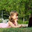 Stock Photo: Little girl lying on grass with laptop