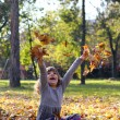 Happy little girl throws leaves in autumn park — Stock Photo