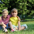 Happy little girl and boy sitting on grass — Foto de Stock