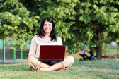 Happy girl with laptop sitting on grass — Stock Photo