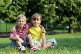 Happy little girl and boy sitting on grass — Stock Photo