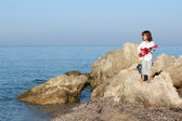 Little girl with guitar standing on a rock — Stock Photo