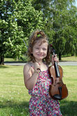 Happy little girl with violin in park — Stock Photo