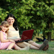 Happy little girl and woman with laptop in park — Stock Photo