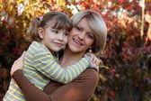 Happy matka a dcera portrét v podzimním parku — Stock fotografie