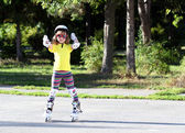Roller skating happy little girl with protective gear — Stock Photo