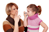 Woman with cigarette and little girl with asthma inhaler — Stock Photo