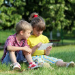 Little girl and boy with tablet in park — Foto Stock