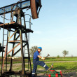 Oil worker with hammer on oilfield — Stock Photo