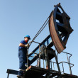 Oil worker climb on pump jack — Stock Photo