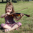 Little girl sitting on grass and play violin — Stock Photo #31927753