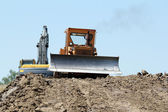 Heavy bulldozer and excavator on road construction — Stock Photo