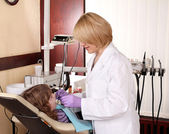 Female dentist and little girl patient in dental office — Stock Photo