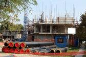 Здание строительной площадки с краном и труб — Стоковое фото