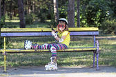 Little girl with roller skates sitting on bench and listening mu — Stock Photo