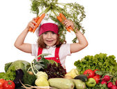 Happy little girl cook with carrots and vegetables — Stock Photo