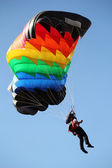 Parachutist with colorful parachute on blue sky — Stock Photo