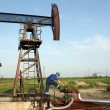 Stock Photo: Oil worker check pump jack pipeline