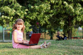 Beautiful little girl with laptop in park — Stock Photo