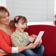 Foto Stock: Happy mother and daughter play with tablet pc