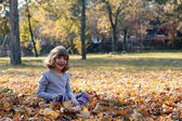 Happy beautiful little girl in autumn park — Stock Photo