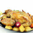 Roasted chicken with potatoes on plate — ストック写真
