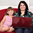 Happy girls with laptop sitting on bed — Stock Photo
